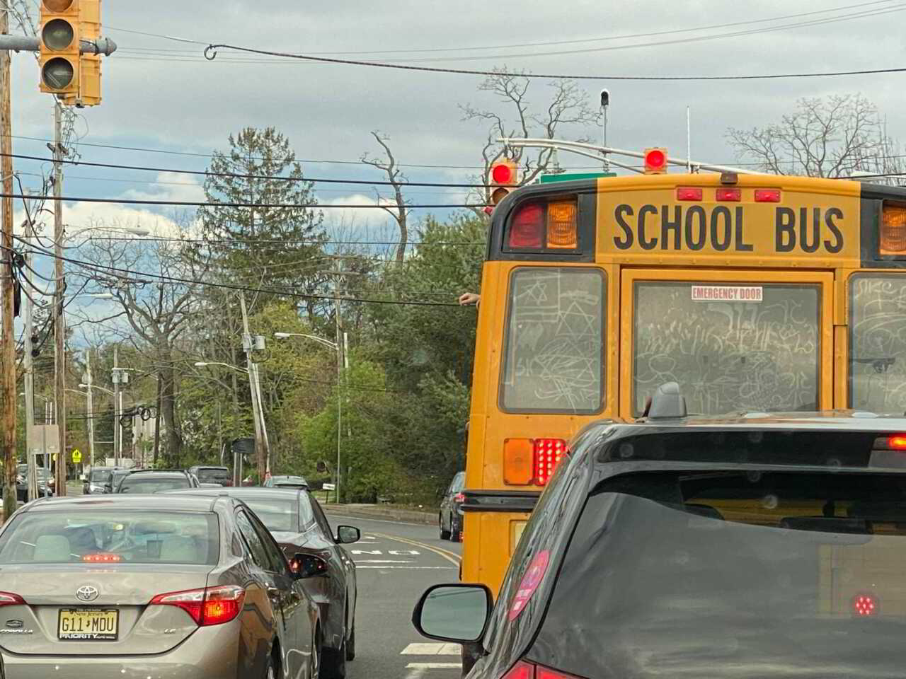 Picture of kids pouring liquid outside the windows of a school bus onto other vehicles. with markings all over the rear windows of the schoolbus.