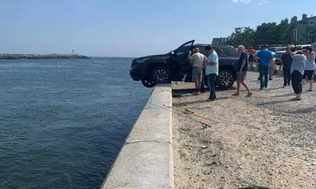 CAR DRIVES OFF PARKING LOT ON WALL OF MANASQUAN INLET